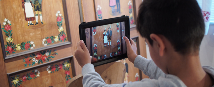 Junge mit Tablet fotografiert Bauernschrank